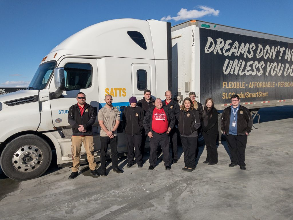 Students and instructors from the CDL examiner class pose by a semi truck used for training