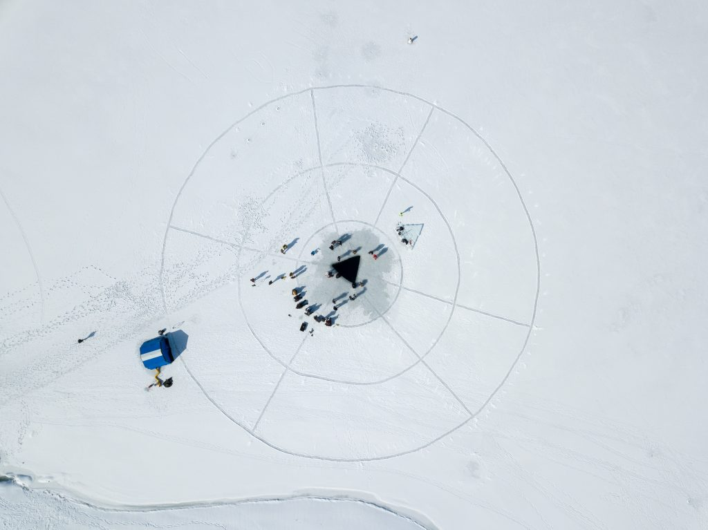 Aerial shot shows the triangle cut in the ice for ice diving training at Deer Creek Reservoir.