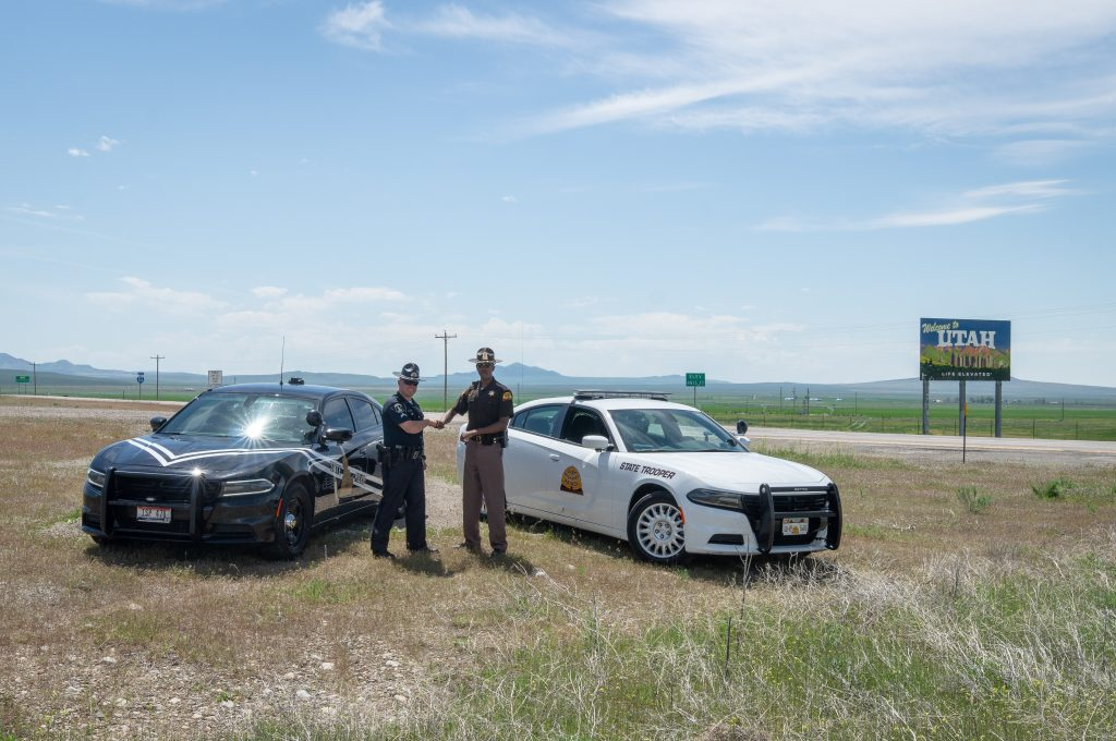 An Idaho State Trooper and Utah Highway Patrol Trooper shake hands at the Utah Idaho border as part of the border to border seat belt enforcement program.