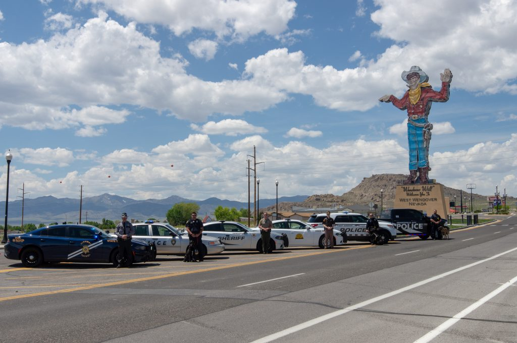 Officers from law enforcement agencies in Utah and Nevada stand by their vehicles with Wendover Will in the background.