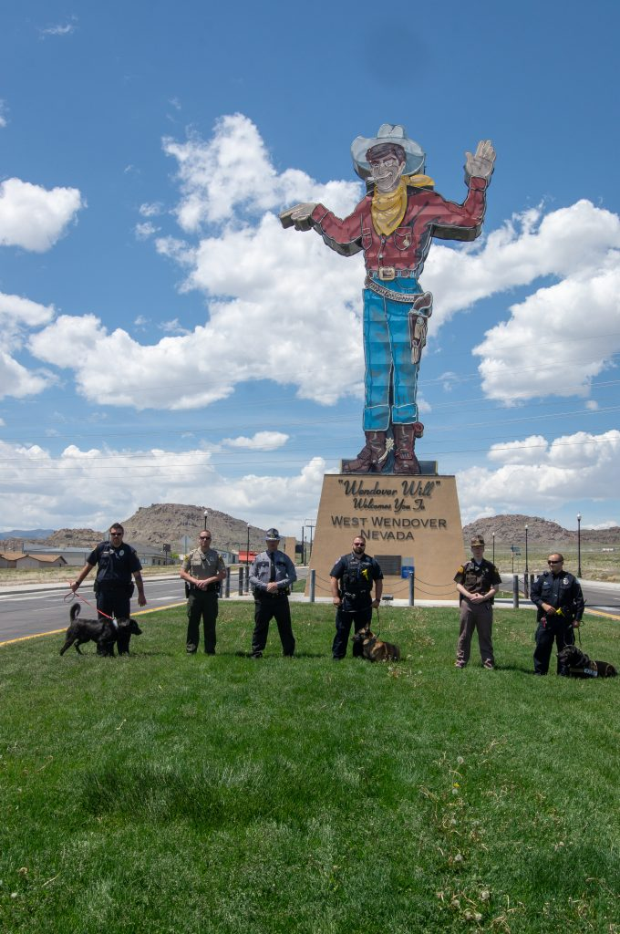 Officers from law enforcement agencies in Utah and Nevada stand with Wendover Will in the background.