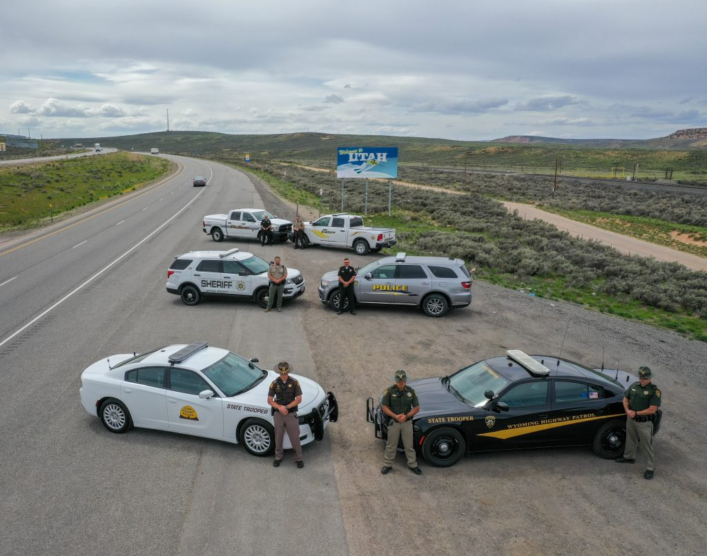 Officers from Wyoming Highway Patrol, Evanston Police Department, Uinta County WY Sheriff's Department, Vernal Police Department, Unitah County Sheriff's Department and Utah Highway Patrol stand by their vehicles with the Welcome to Utah sign in the background.