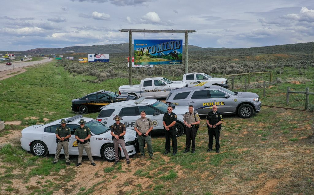 Officers from Wyoming Highway Patrol, Evanston Police Department, Uinta County WY Sheriff's Department, Vernal Police Department, Unitah County Sheriff's Department and Utah Highway Patrol stand by their vehicles with the Welcome to Wyoming sign in the background.