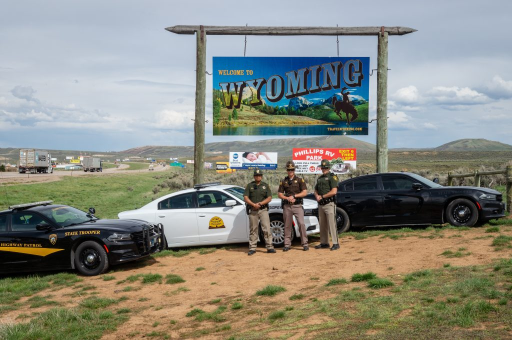 Wyoming Highway Patrol and Utah Highway Patrol stand by their vehicles with the welcome to Wyoming sign in the background,