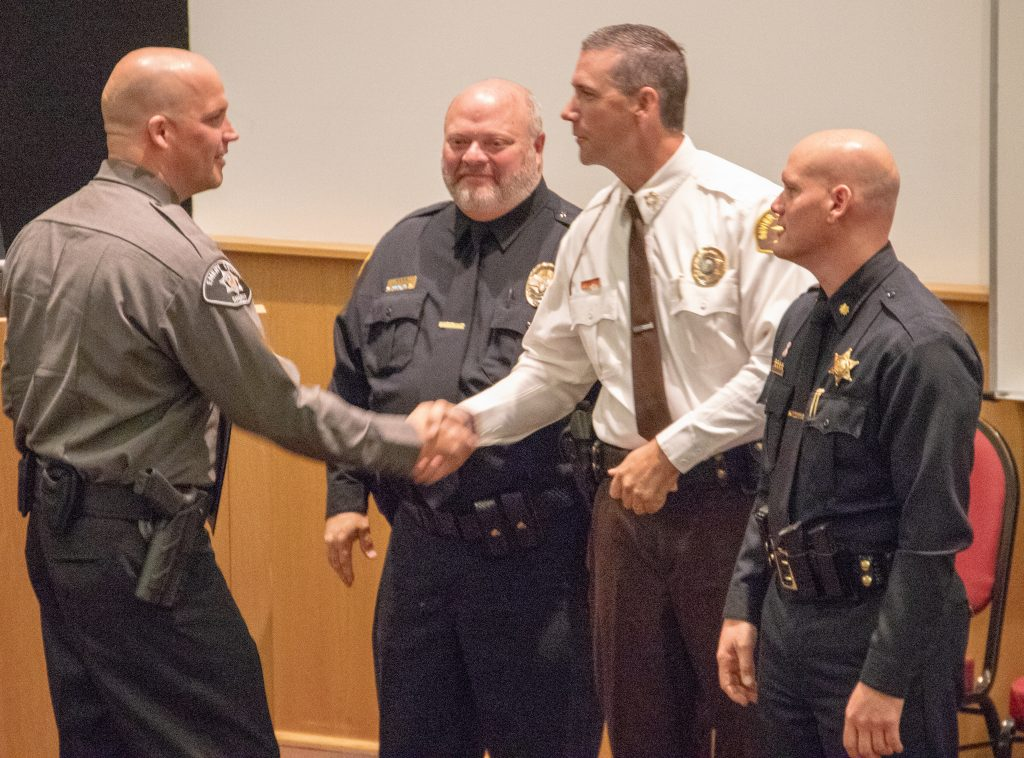 New Emery County deputy shakes hands with Sheriff Curtis at POST graduation.