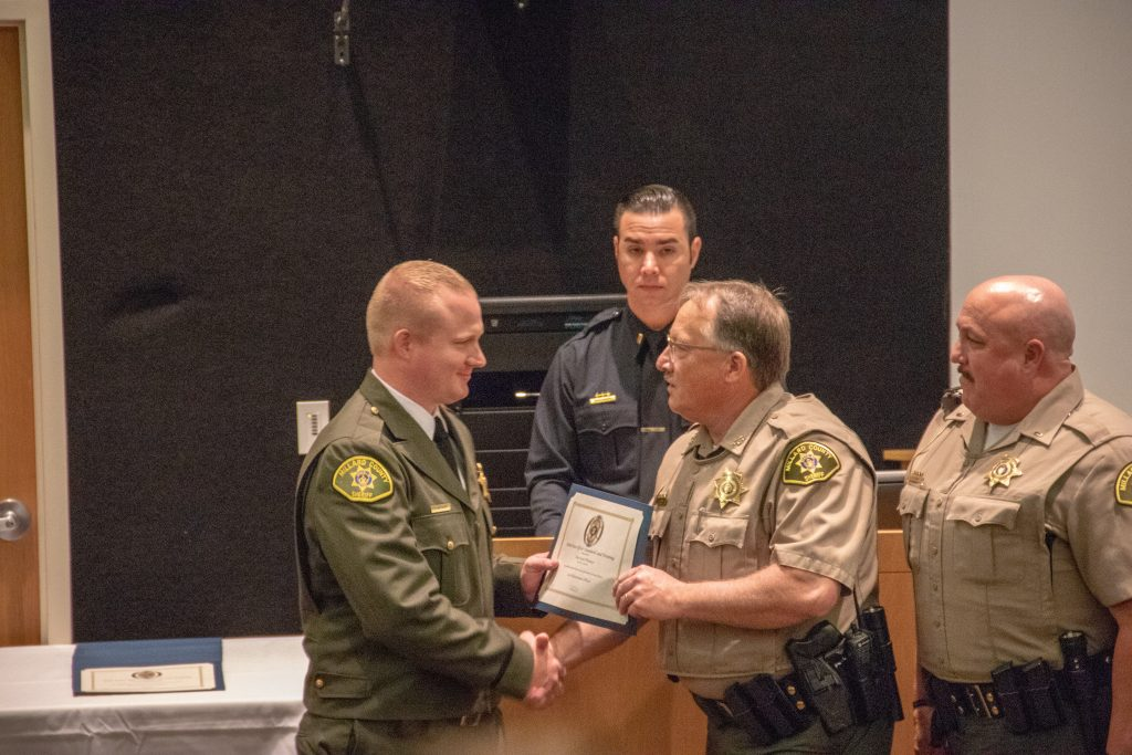 New deputy shakes hands with sheriff from his new agency at POST graduation