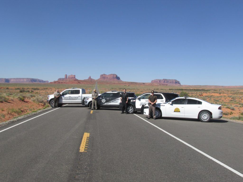 San Juan County Sheriff Deputy, Arizona State Troopers, Blanding City PD and IUHP Trooper stand by their vehicles with Monument Valley in the background.