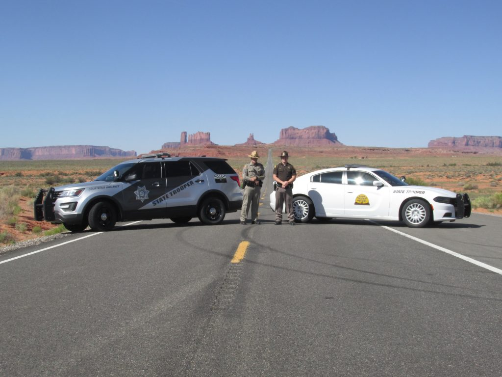 An Arizona State Trooper and UHP Trooper stand by their vehicles with Monument Valley in the background.
