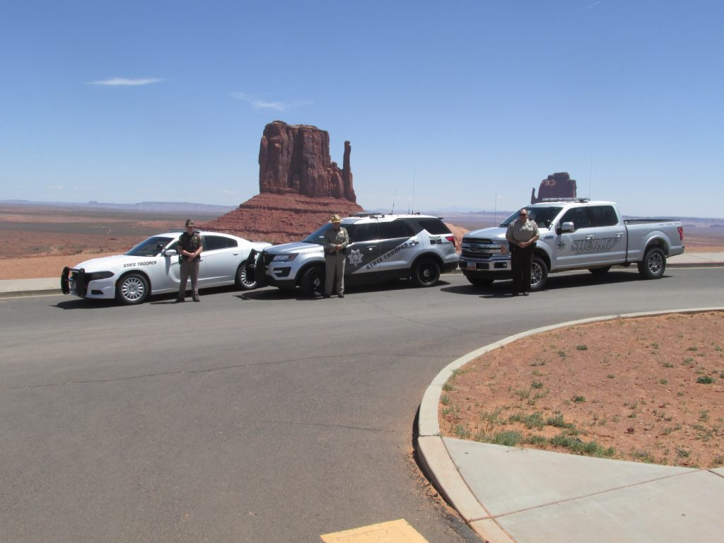 UHP Trooper, San Juan County Sheriff Deptuy and Arizona State Trooper stand by their vehicles at 4 corners.