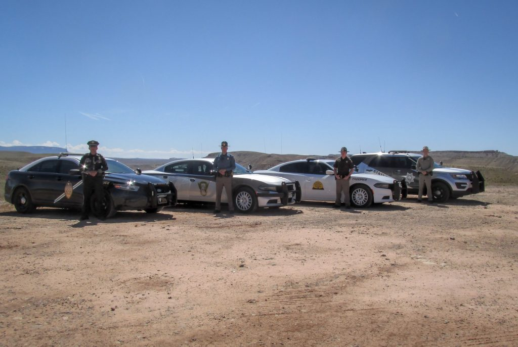 State troopers from New Mexico, Colorado, Utah and Arizona stand by their vehicles.