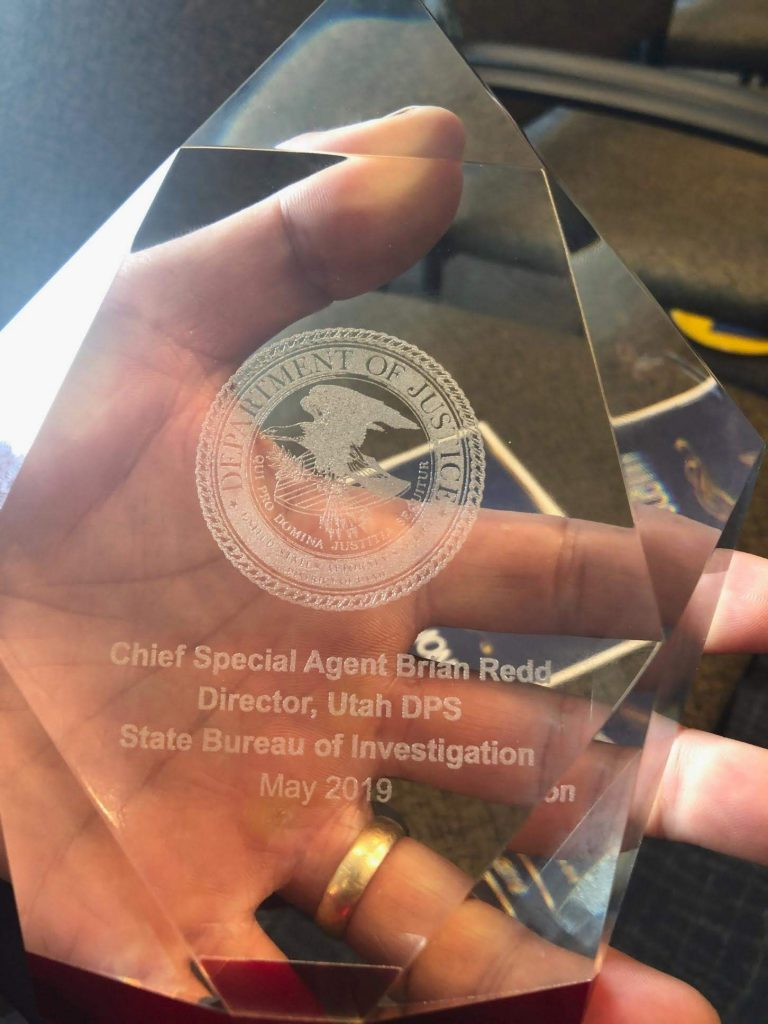 Chief Redd holds the award he received from the US Attorney