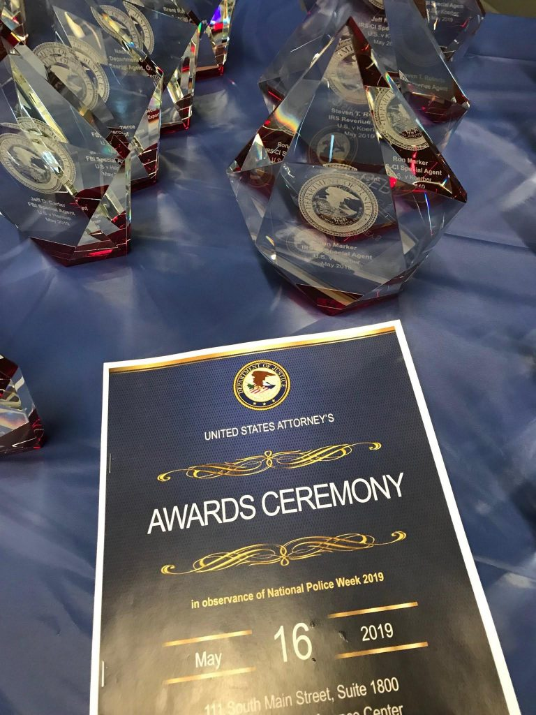 Cover of program for US Attorney's Awards Ceremony with awards in the background.