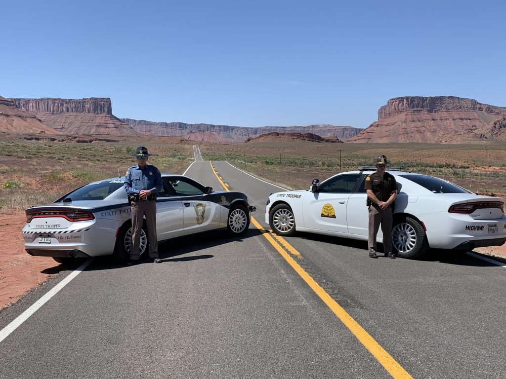 UHP and CSP Tropers stand by their vehicles with Monument Valley in the background.