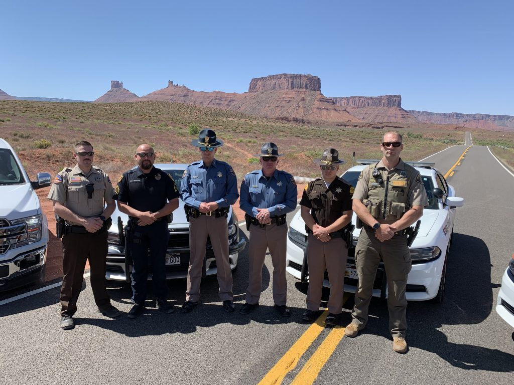Grand County Sheriff, Colorado State Patrol, UHP, Moab City Police and San Juan County Sheriff stand by their vehicles with Monument Valley in the background