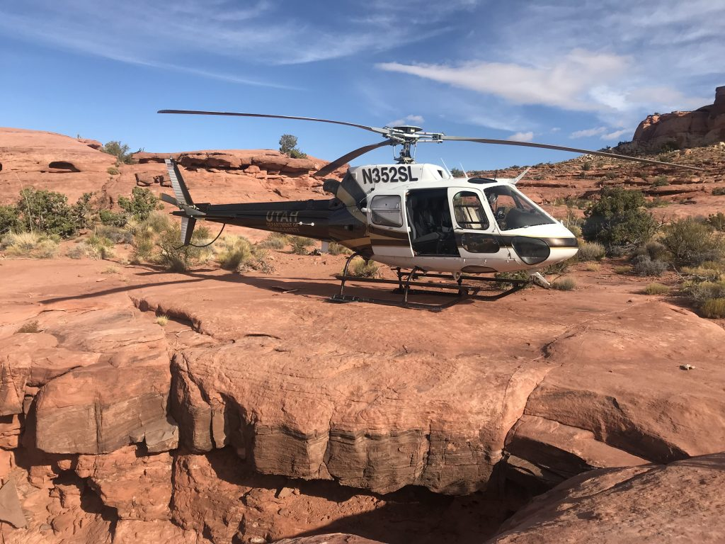 The DPS helicopter landed on red rock during a rescue procedure.