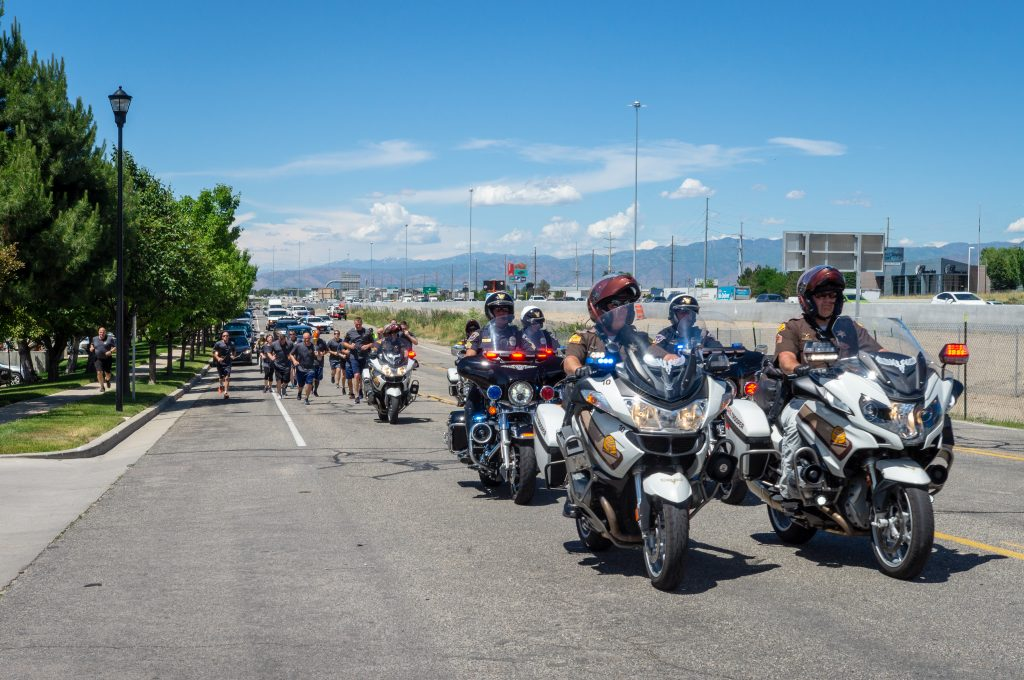 UHP and West Jordan motors lead the way for DPS runners on the Special Olympics Torch Run.
