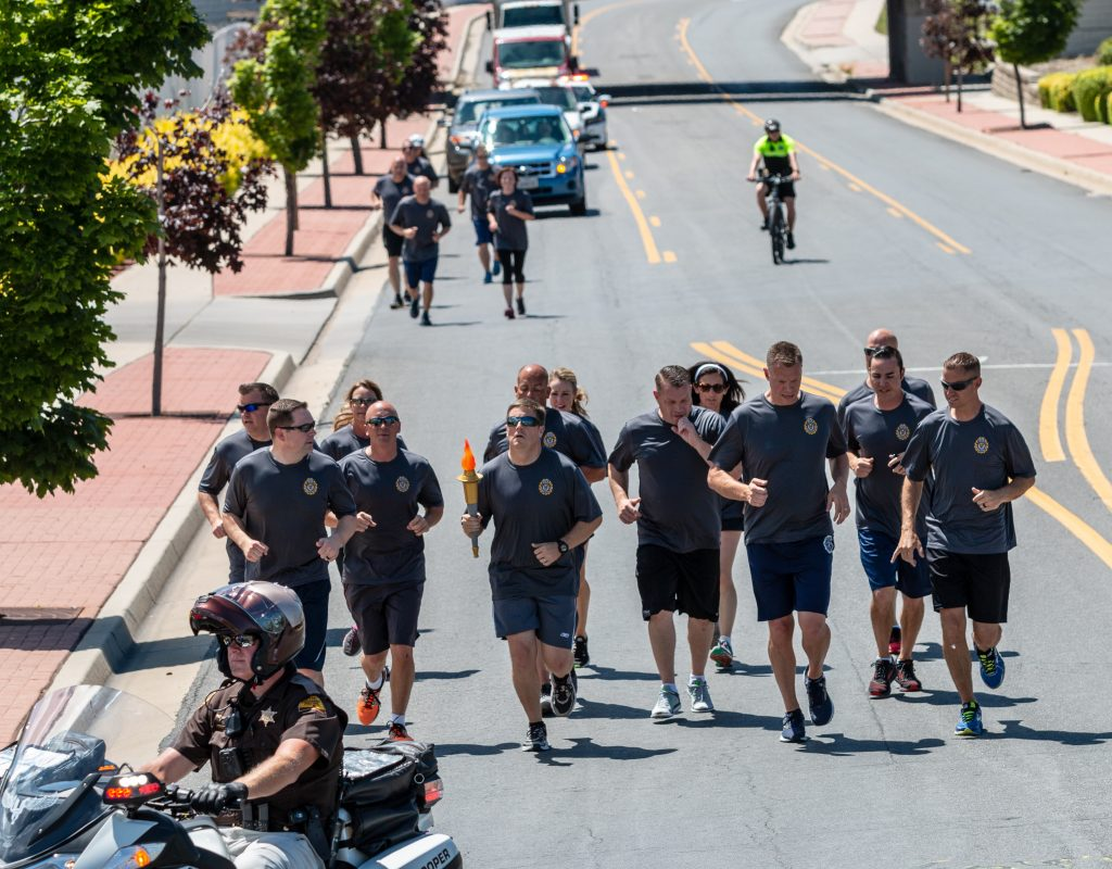 UHP PIO Nick Street holds the torch and runs with the group during the Special Olympics Torch Run.