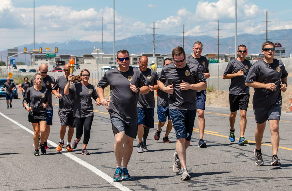 Deputy Commissioner Kristy Rigby holds the torch and runs with the group during the Special Olympics Torch Run.