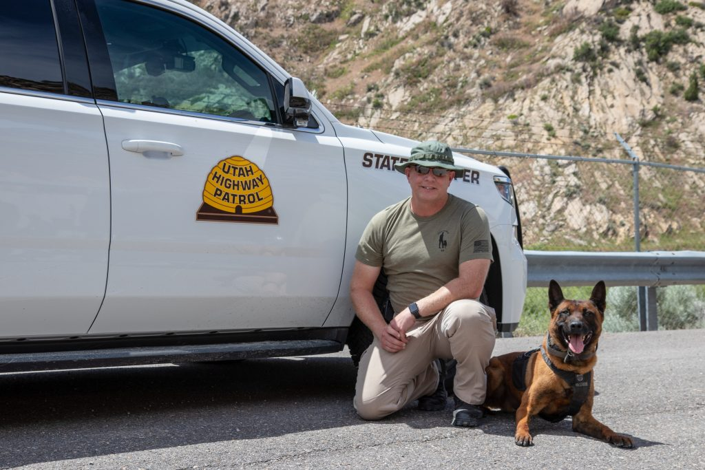 Trooper Elmer poses next to K9 Rocco by Trooper Elmer's UHP vehicle.