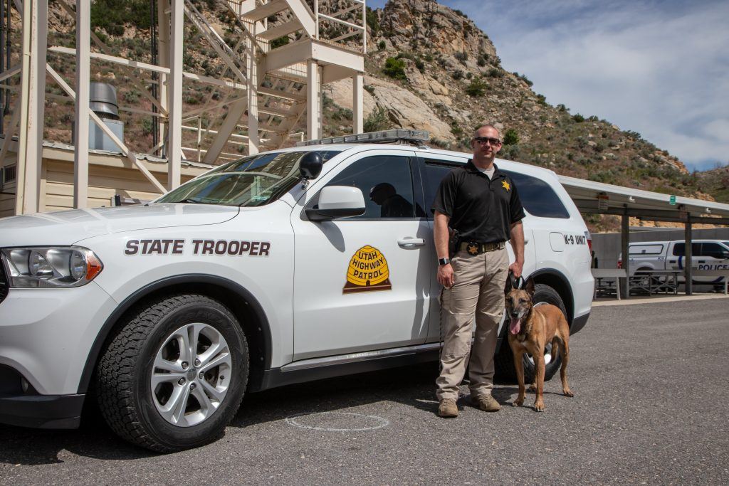 Trooper Colvin stands next to Arros by Trooper Colvin's UHP Vehicle.