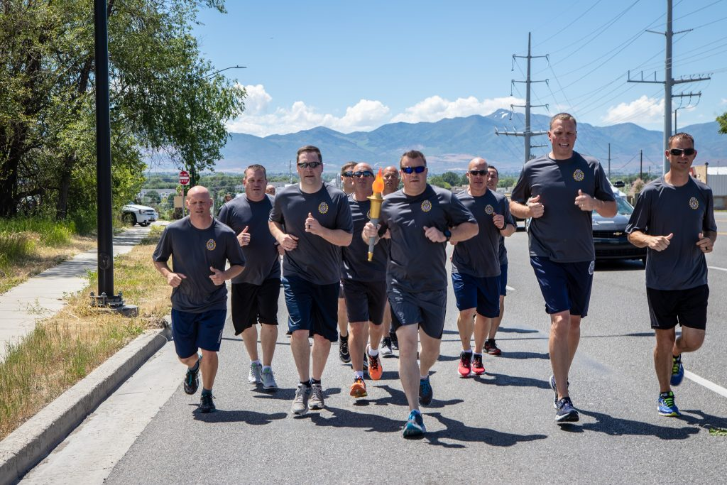 UHP Major Kotter holds the torch and runs with the group during the Special Olympics Torch Run.