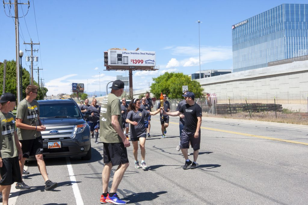Assistant Attorney General hands off the torch to the South Jordan team during the Special Olympics Torch Run
