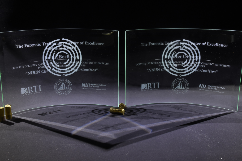 The awards presented to Justin Bechaver and Jennifer Gelston are curved etched glass.