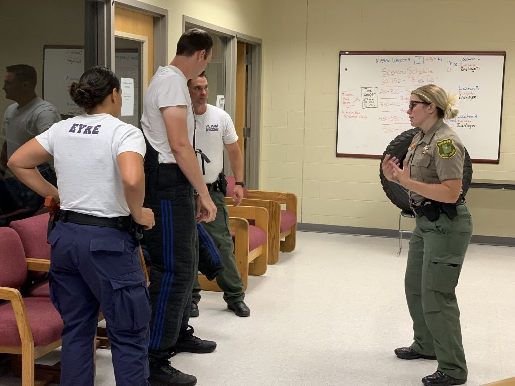 Deputy Wennegren gives directions to a cadet who is putting on a bite suit.