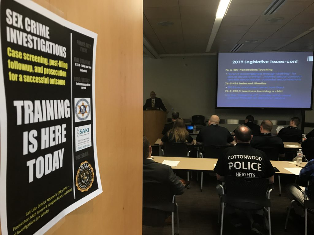 Sex crimes investigators attend a class at which they received a legislative update. Photo shows flyer announcing training and officers listening as Matt Janzen from the Salt Lake County DA's Office provides them with information.