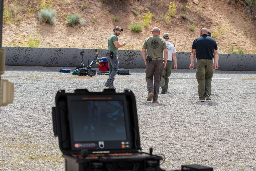 Utah Bomb Squad Task Force members participate in a training scenario, walking out to suitcases placed on a shooting range.