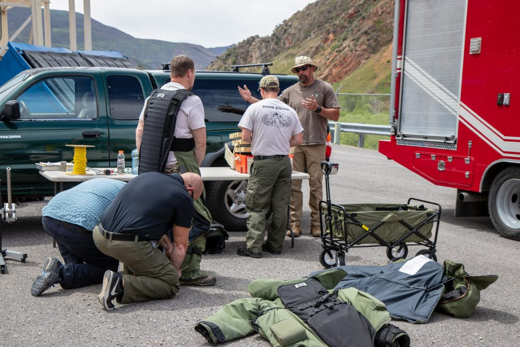 Utah Bomb Squad Task Force members participate in a training scenario - and assist one member with putting on a bomb suit.