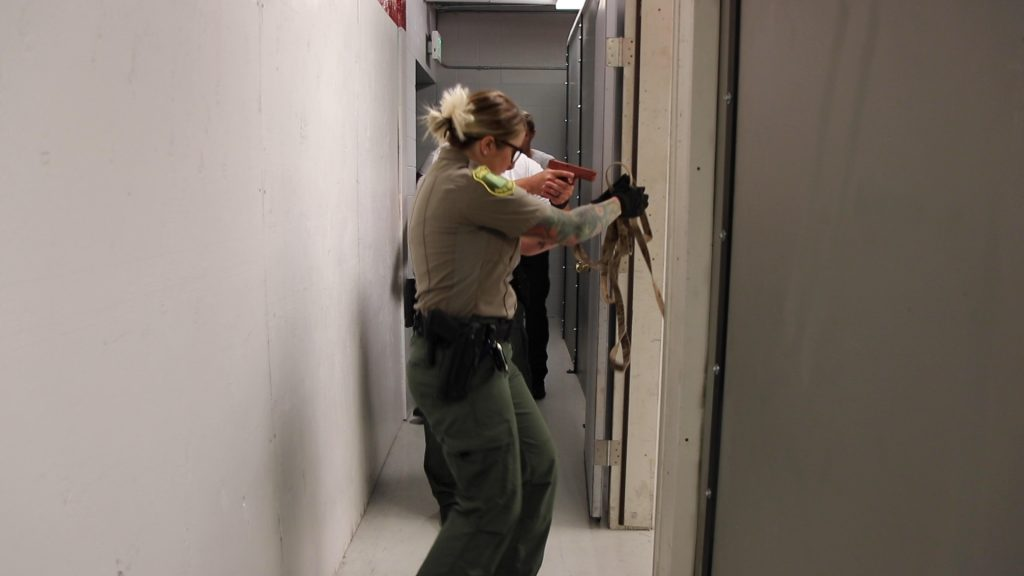 Deputy Wennegren demonstrates room clearing techniques to cadets as they follow K9 Nomos into the room.