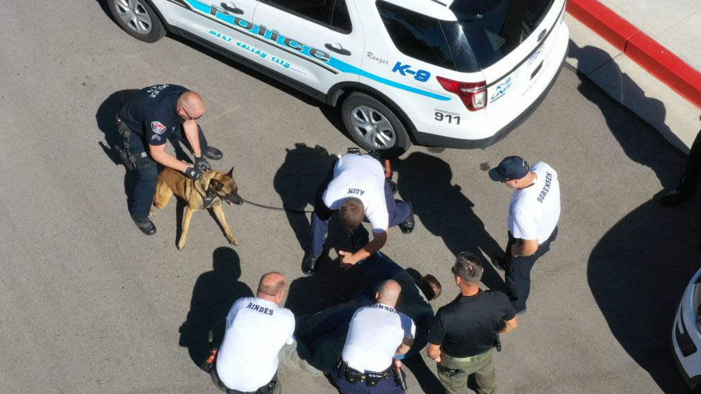 Aerial view of cadets holding down the cadet in a bite suit, who was the suspect, preparing to handcuff him, as Sgt. Palmer holds K9 Ranger.