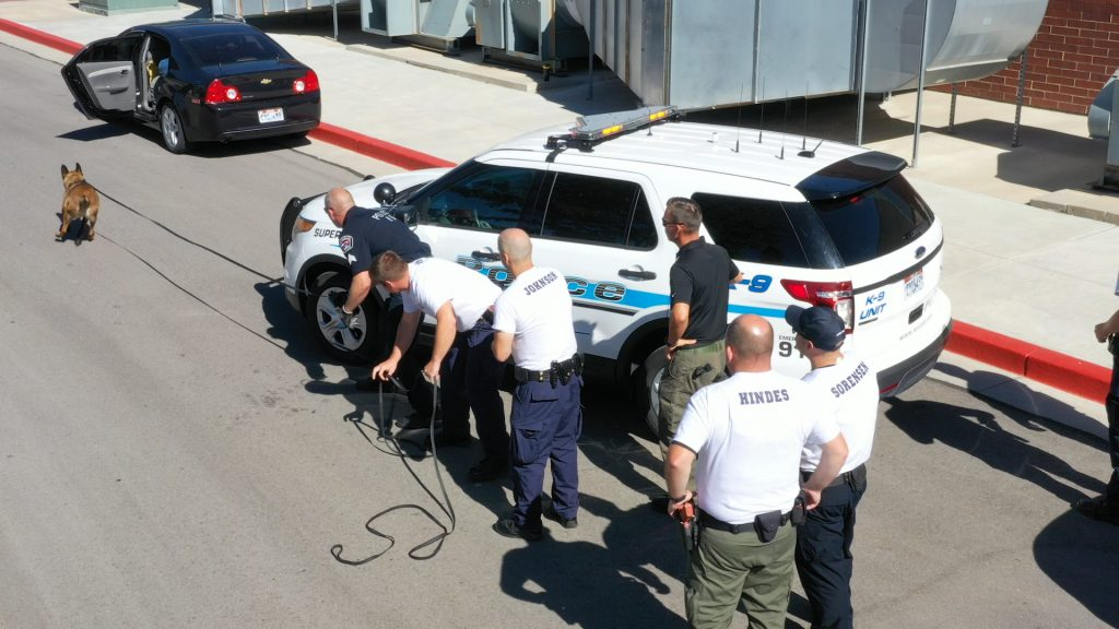 Aerial view of K9 Ranger running toward the suspect vehicle, as cadets look on.