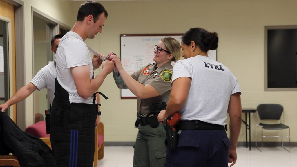 Deputy Wennegren helps a cadet put on the bite suit.