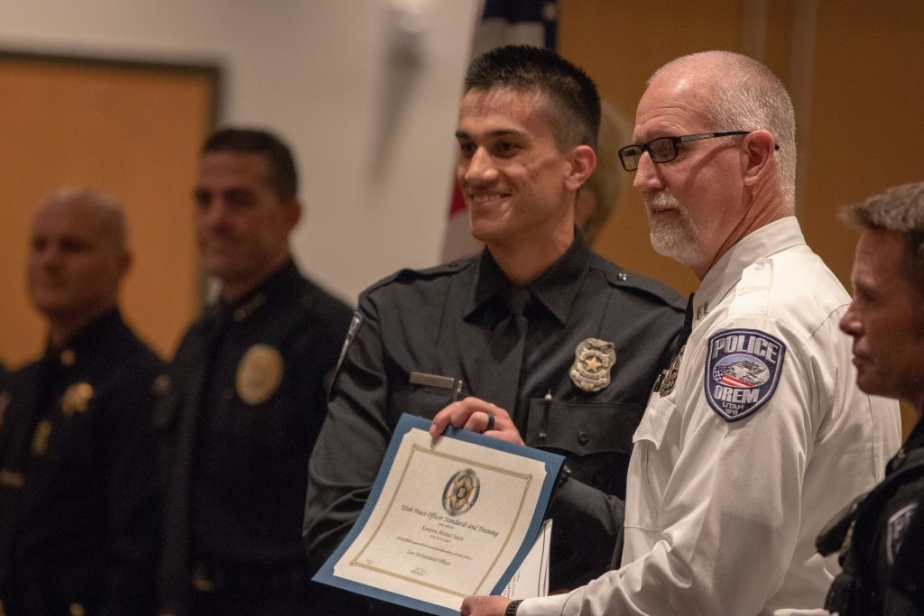 A new Orem officer stands with the chief of Police of Orem and holds his certificate.