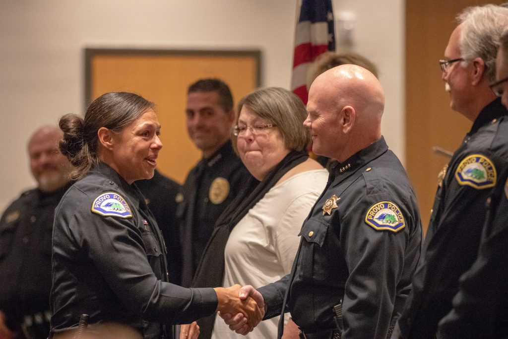 A graduating female cadets shakes hands with the chief of police of Provo.