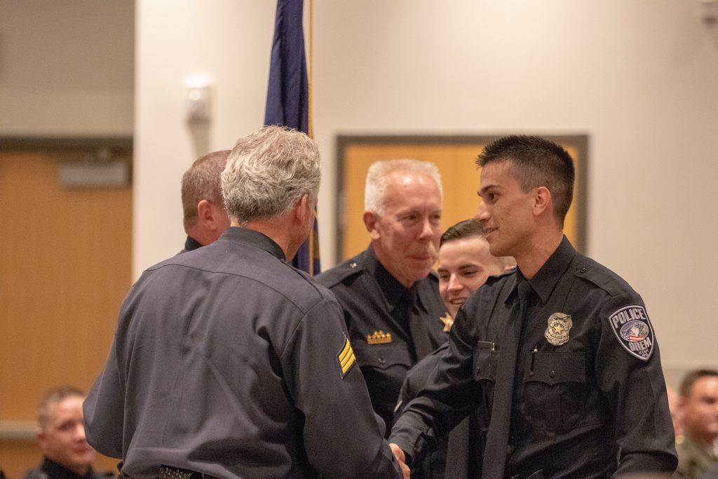 Orem Officer Juarez and Enoch Officer Mackelprang shake hands with the POST staff as they receive the High Academic Award.