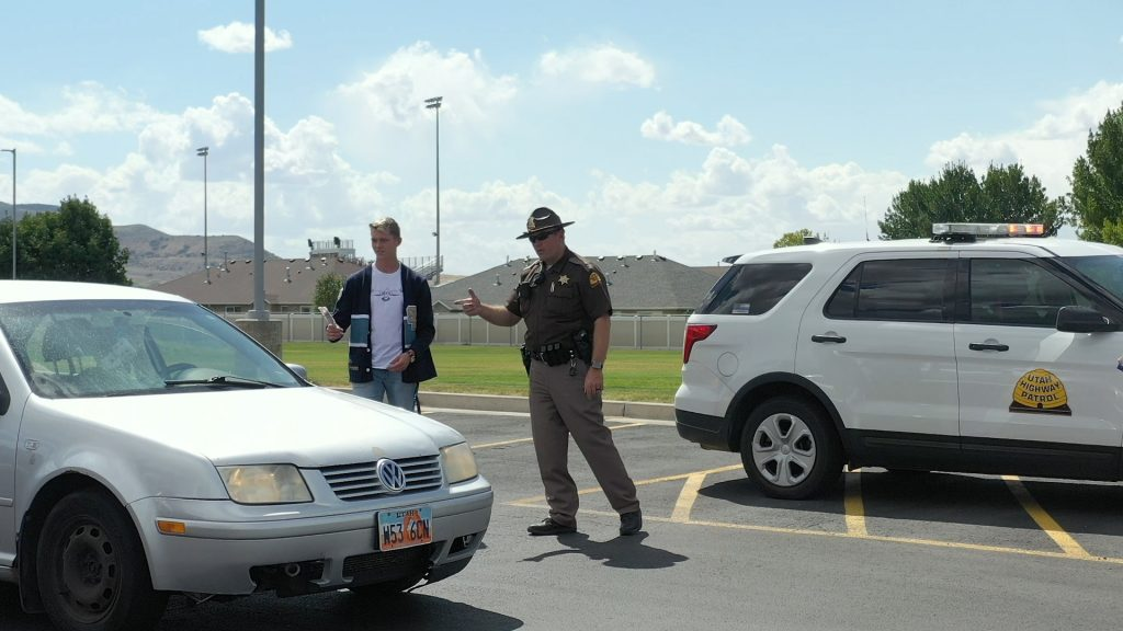 A UHP Trooper and Salem Hills student body officer talk to the driver of a vehicle and offer a Creamie.