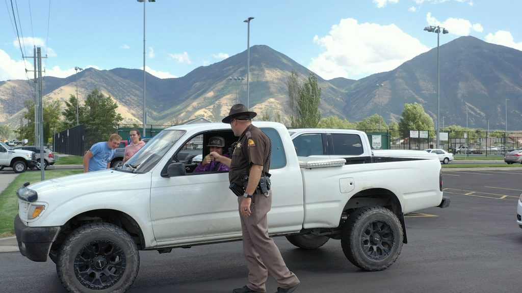 UHP Trooper gives a fist bump to a seat belted driver as he exits the Salem Hills High parking lot.