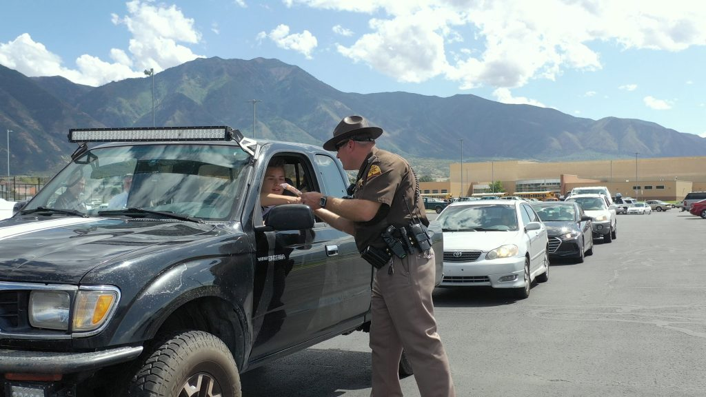 UHP trooper shakes the hand of a seat belted driver and offers him a Creamie.