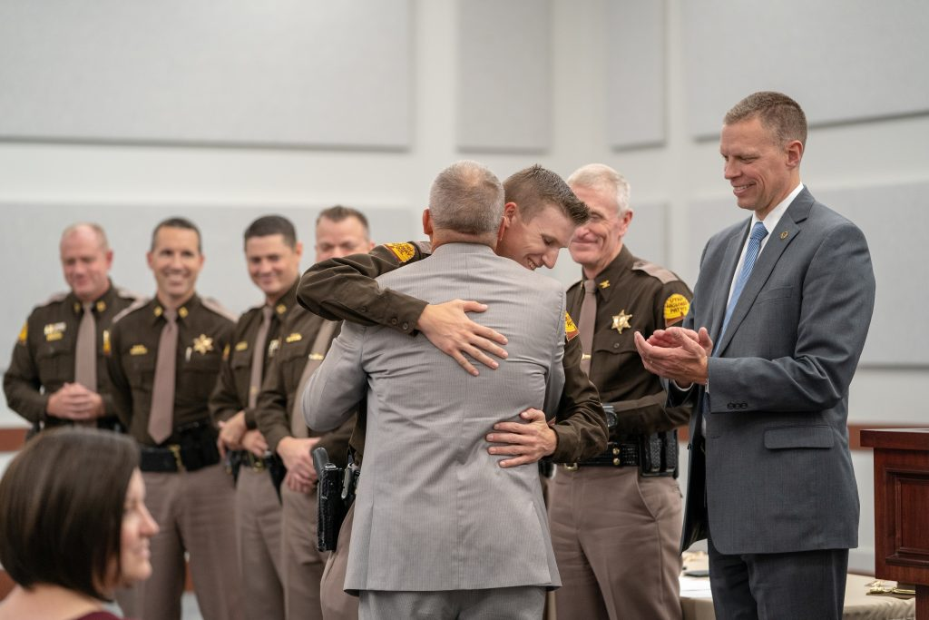 New Trooper embraces his relative who just pinned his badge on him.