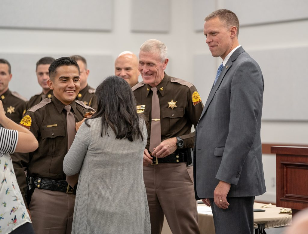 A New Trooper smiles as his wife pins his badge on him and Colonel Rapich and Commissioner Anderson look on.