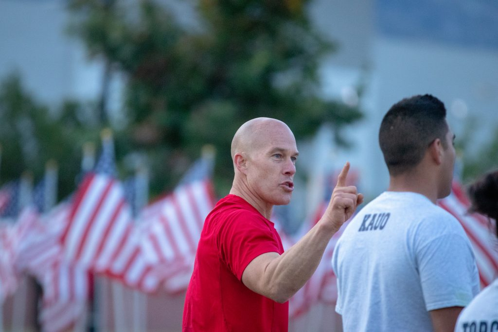 Sgt. Lauritzen gives instructions for the PT session to the cadets. He and the back on one cadet are in focus while the background is filled with American flags.