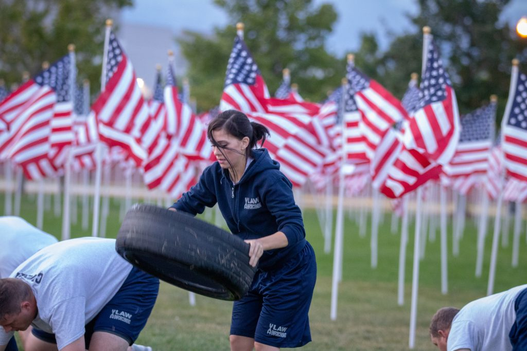 A female cadet prepares to put the tire on the ground and do a push up on it.