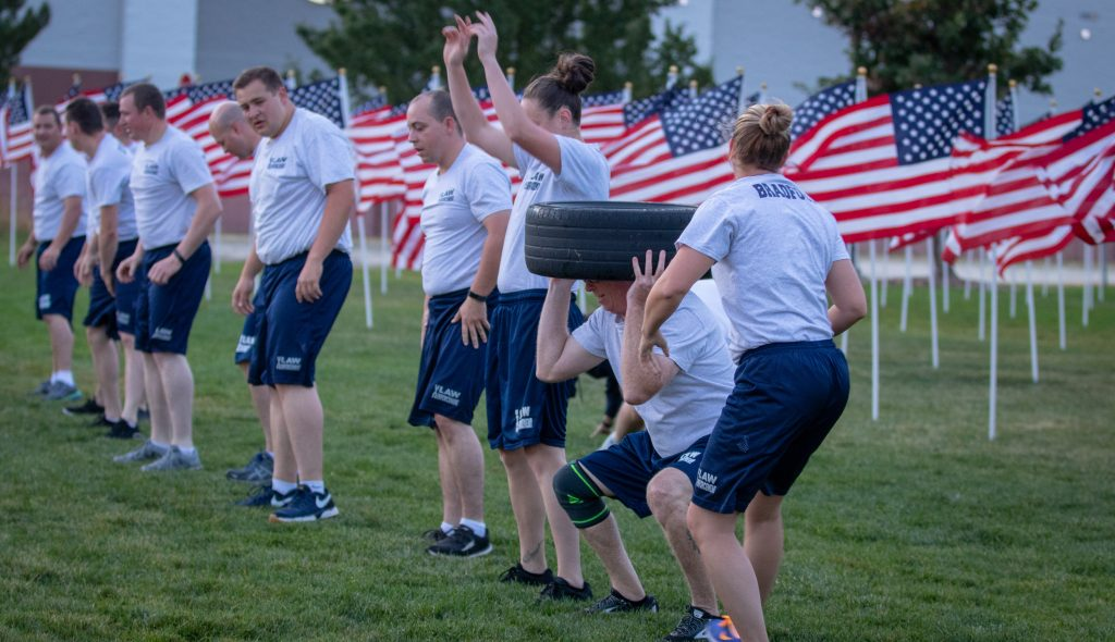 The line of cadets participating in the PT session - one cadet has just passed the tire to another and the others are doing burpees.