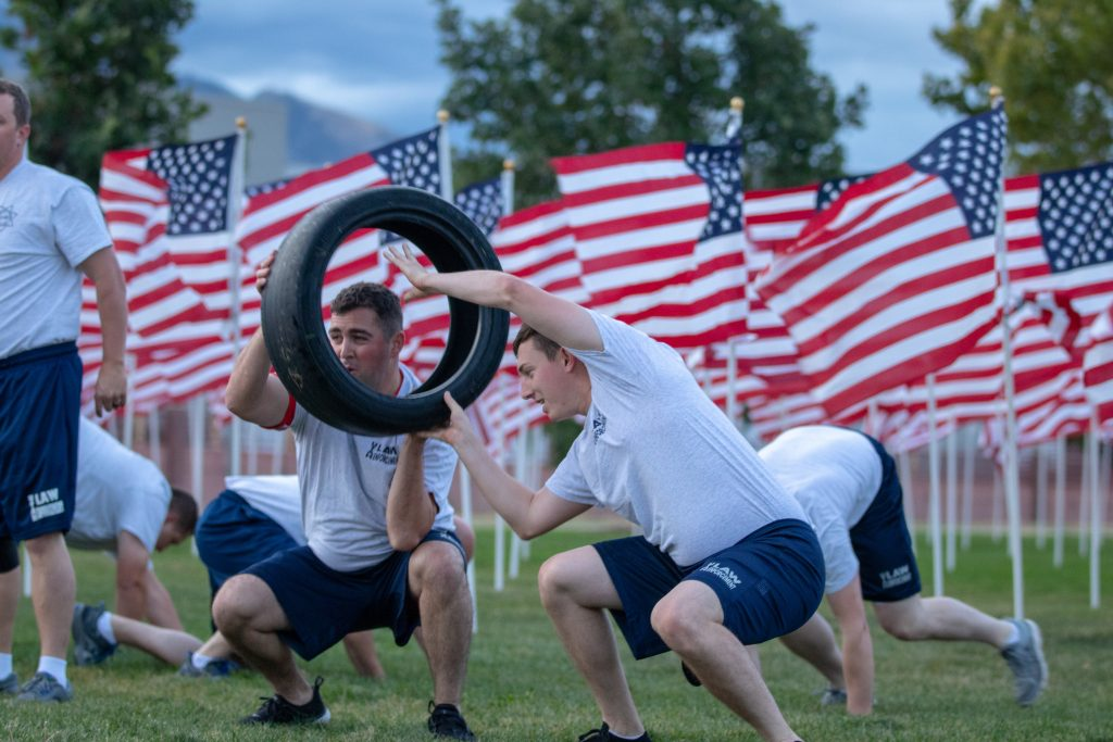 Cadets participate in the PT session and two are passing a tire to each other while performing squats. In the background, other cadets crab walk to the end of the line and the background is American flags.