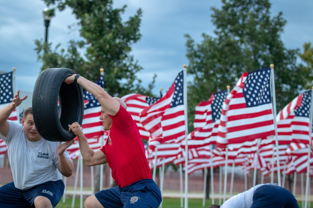 Sgt. Lauritzen passes the tire to a cadet with American flags in the background.