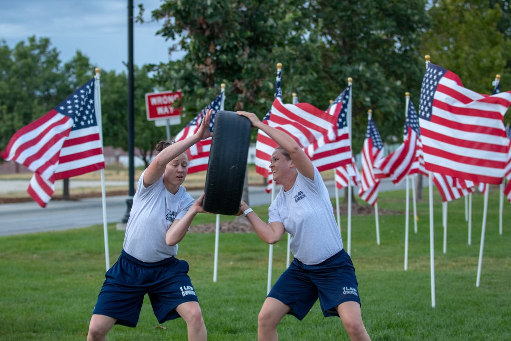 Two female cadets pass the tire to each other with American flags in the background.