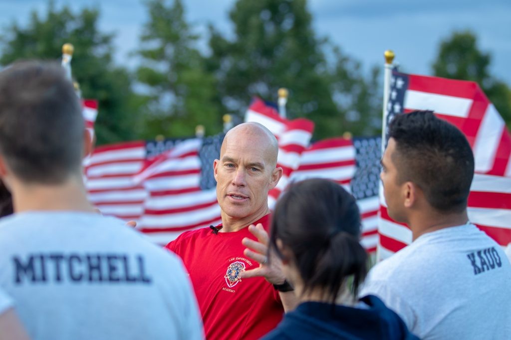 Sgt. Lauritzen discusses the meaning of the Healing Field with the cadets. He is pictured with American flags in the background and cadets in a semi circle in the foreground.